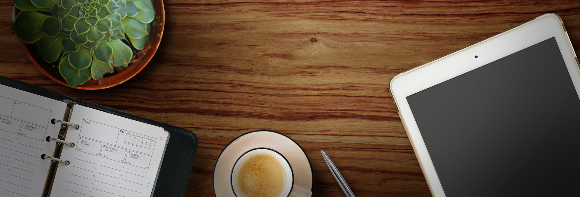 header image with wood background, notebook, coffee cup, plant, ipad